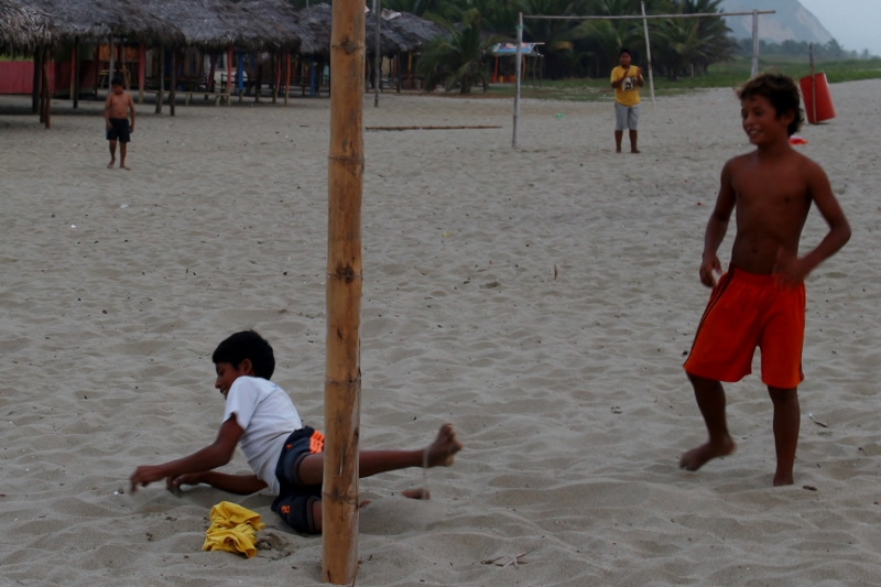 Children playing football on the beach all day, every day.